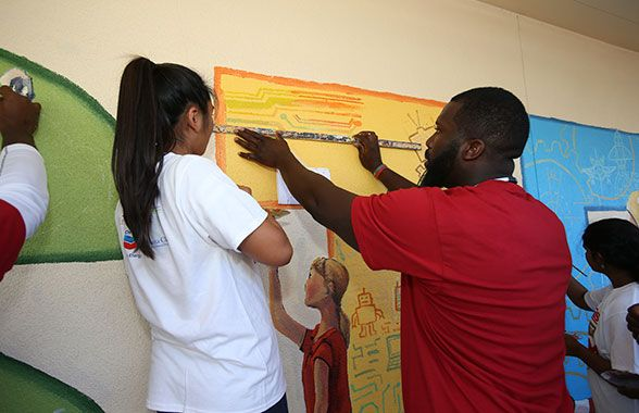 "DT Quinton Dial works with a Cabrillo Middle School student to perfect the technology representations in the ""T"" of the STEM mural."