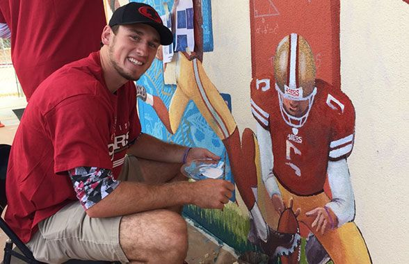 "P Bradley Pinion puts the finishing touches on his likeness as part of the ""Science of Football"" theme of the mural."